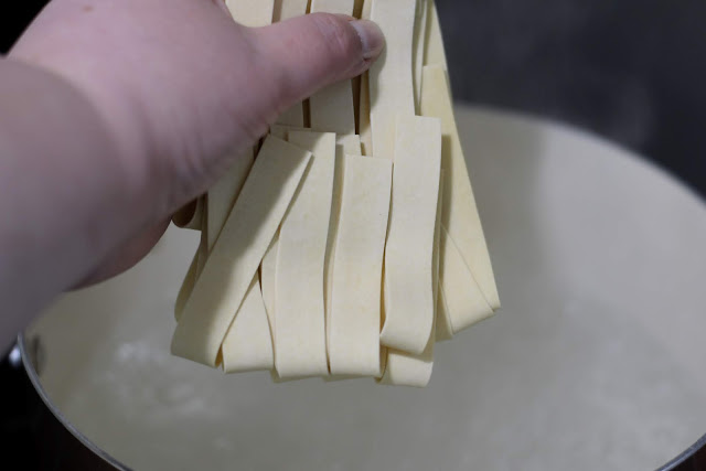 The pasta being added to the boiling water on the stove.