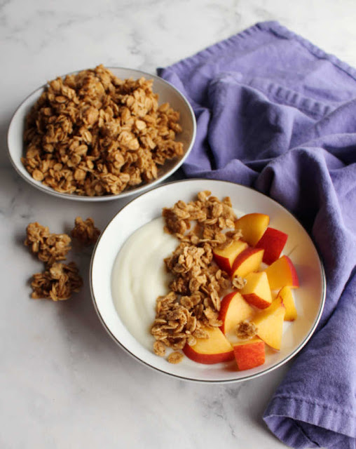bowl of yogurt with peaches and granola next to a bowl filled with homemade granola