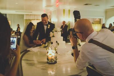 Novios cortando la tarta mientras el fotógrafo y una invitada con móvil les hacen una foto