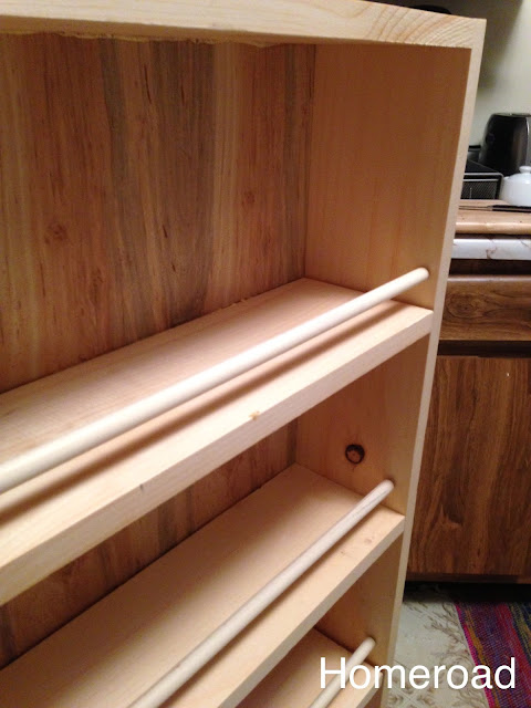 wooden shelves and dowels to hold the food onto the shelves when storage slides between the cabinets