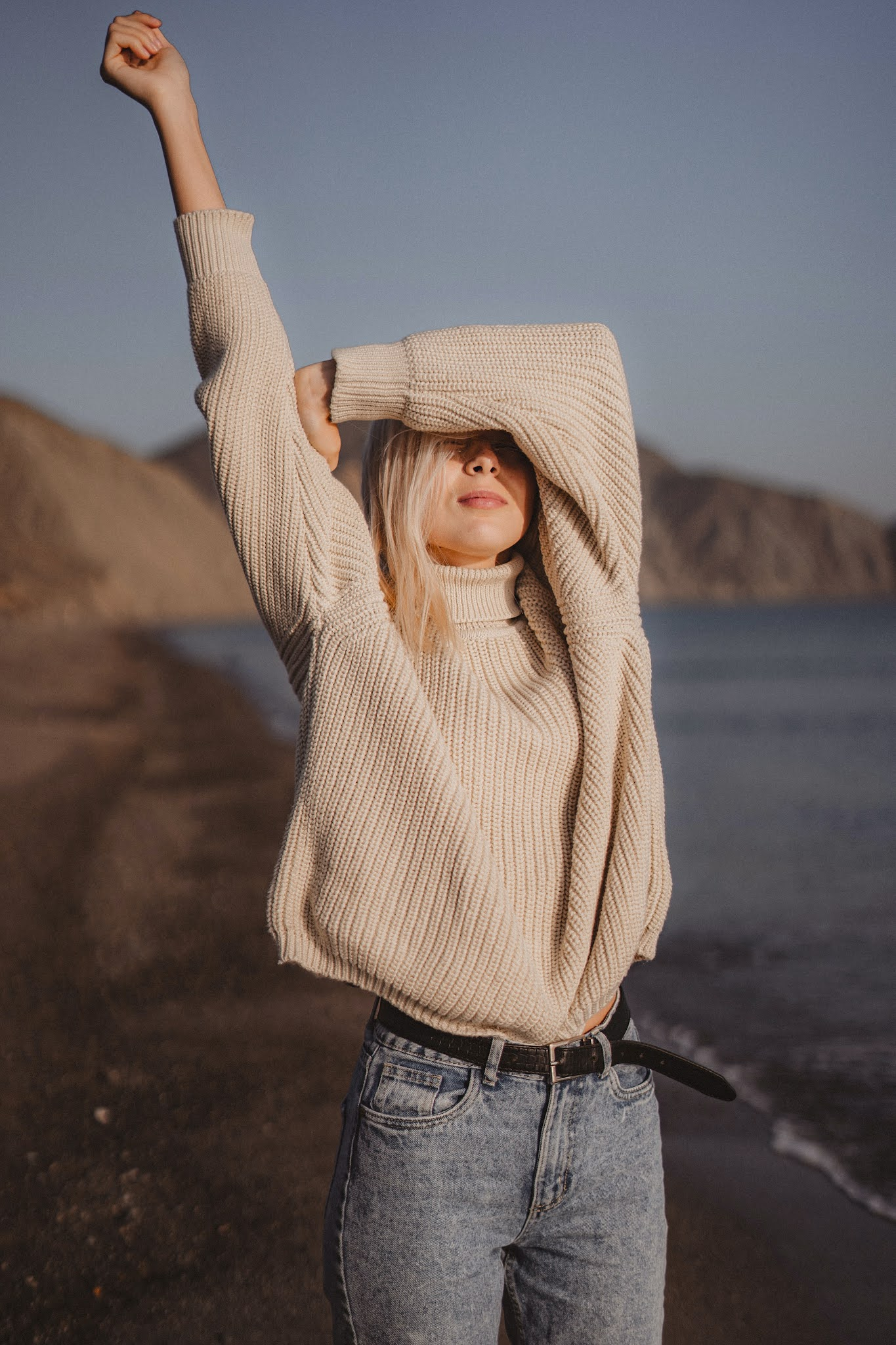 woman on a beach in knit sweater