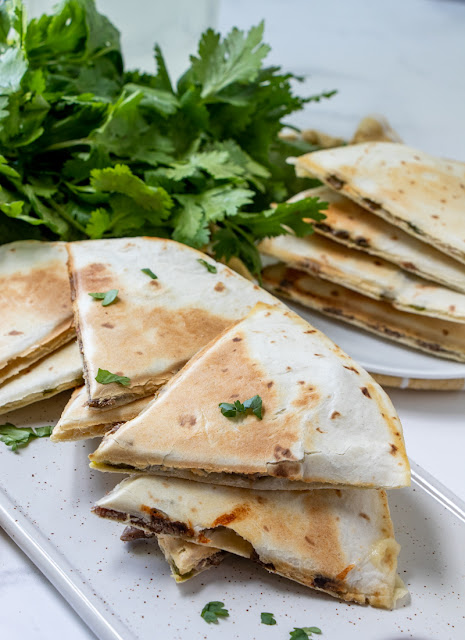 Philly Cheesesteak Quesadillas two plates with parsley