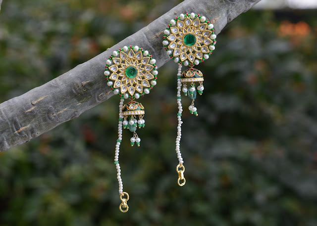 A pair of earrings stuck on a tree for display.