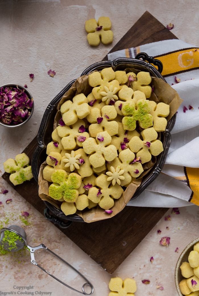 eggless saffron cookies shaped in flower, served on a wooden board in metal tray