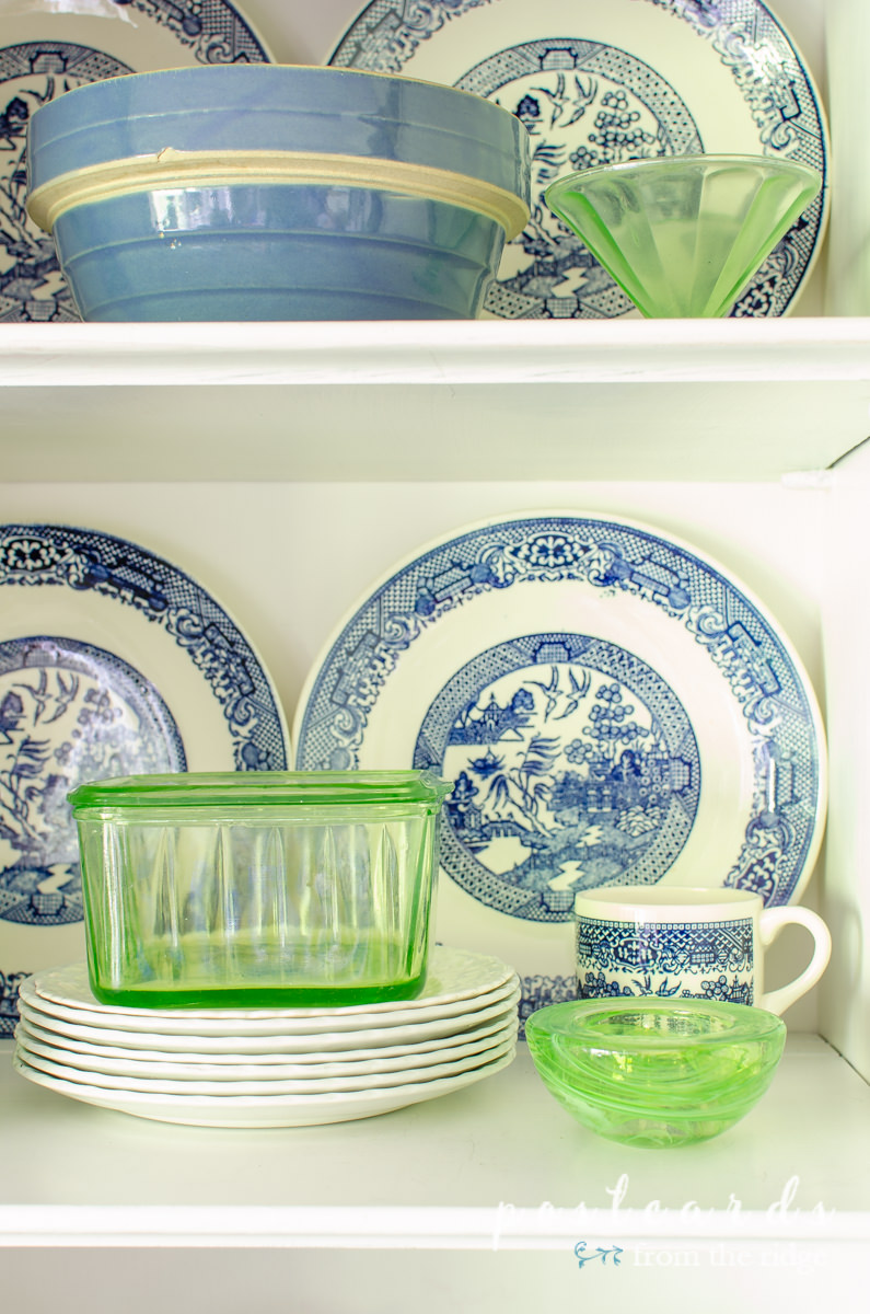 green depression glass and blue willow dishes in a painted china cabinet