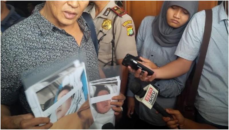 Edi Darmawan Salihin menunjukkan foto anaknya saat meninggal