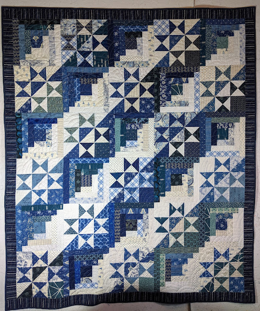 This scrap quilt alternates Log Cabin and split Ohio Star blocks to create a straight furrow design diagonally across the surface.