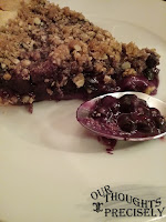 A close shot of a slice pf blueberry pie on a white plate. Some of the pie is on the spoon, which is also on the plate..