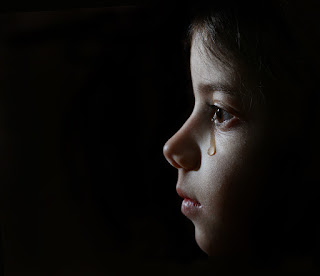 A young girl crying in a dark room.