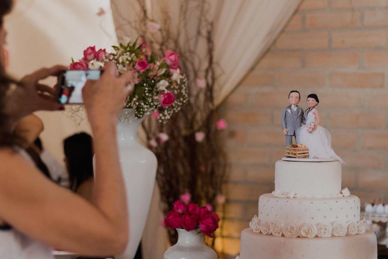 convidada fotografando bolo casamento