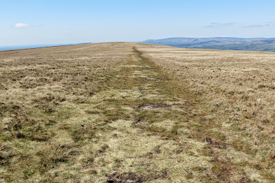 A long ridge of bare grass stretching into the distance under blue skies.