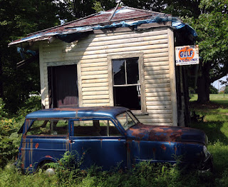 Vintage station wagon next to old wooden building.
