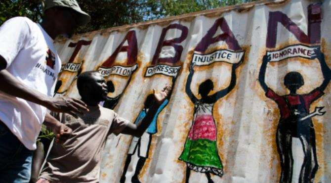 Painter Thomas Dai (L) and musician James Aka, both members of the new activist movement #AnaTaban, talk in front of Thomas' latest graffiti in a street in Juba, South Sudan. By Albert Gonzalez Farran (AFP/File)