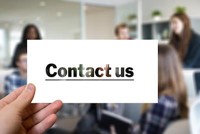 """Persona sosteniendo un cartel con el lema """"Contact us"""""""