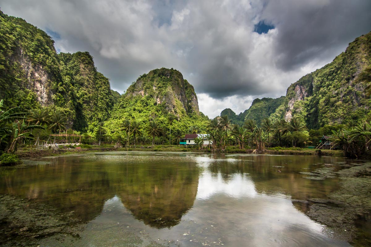 Limestone cliffs reflect in the water ponds in Berua Village, Rammang Rammang