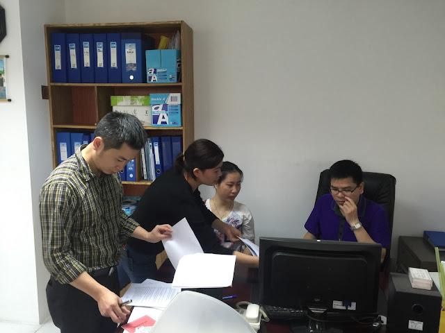 Anh Vũ Hoài Linh - Công Chứng Viên (áo kẻ) đang kiểm tra hợp đồng của khách hàng