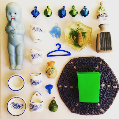 Flatlay of vintage dolls' house miniatures in blue and green colours.