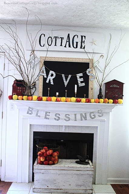 Mantle decorated in the farmhouse style with chalkboard, cottage sign, red and yellow apples, barn platter, red mailbox, blessings sign and harvest sign | Minimalist Farmhouse Apple Mantel | rosevinecottagegirls.com