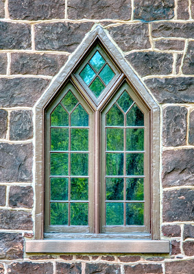Gothic window with point at the top set into brown stone wall. Green leaves of a nearby tree are reflected in the glass.