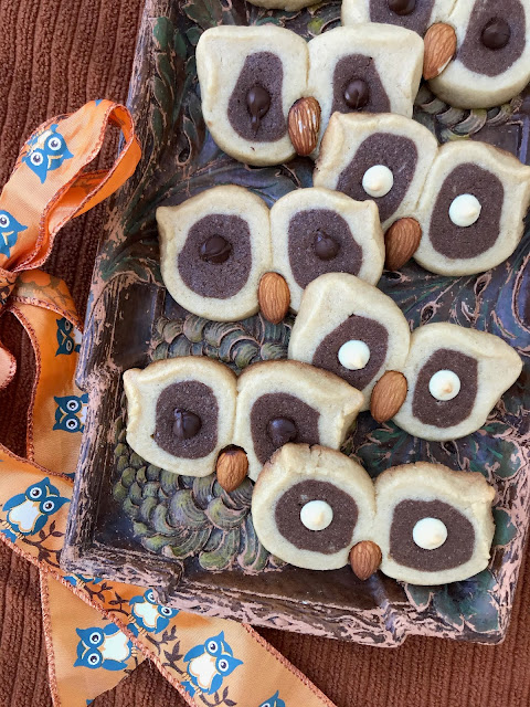 Tray of finished chocolate and almond owl eye cookies with a ribbon with owls and branches.