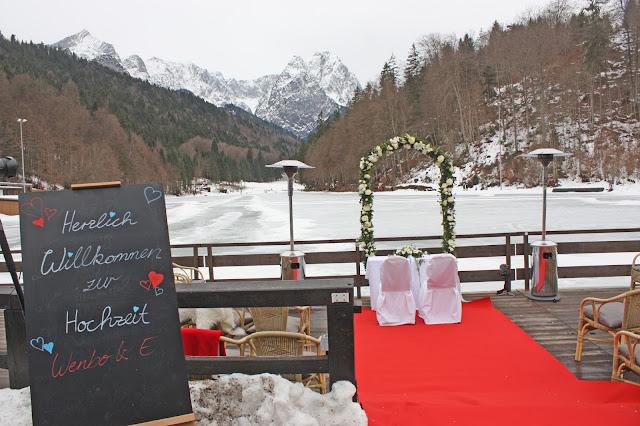 Trauzeremonie am See im Winter, Eisblau und Leuchtrot, Winterhochzeit in den Bergen von Bayern, Riessersee Hochzeitshotel Garmisch-Partenkirchen, Winter wedding in Bavaria, Germany