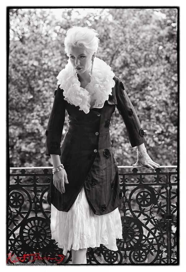 Black and white photograph, full length fashion shot of a model on a  veranda with cast iron Sydney lace wearing a balc jacket and dress with ruffled collar. Photographed by Kent Johnson, Sydney, Australia.