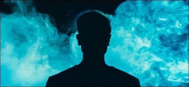 صورة ظلية لفرد أمام دخان أزرق فوق خلفية داكنة.
