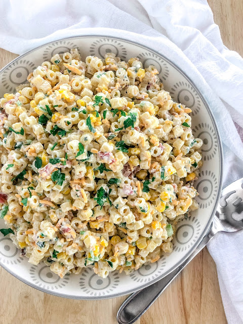 pasta salad with corn bacon cheese and parsley in a white bowl