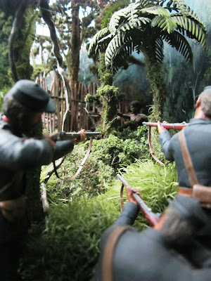 Diorama of 19th-century soldiers with muskets in the bush, aiming at a Maori by a pa fence.