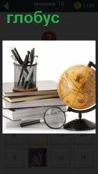 Стопка книг с лупой и глобусом на столе