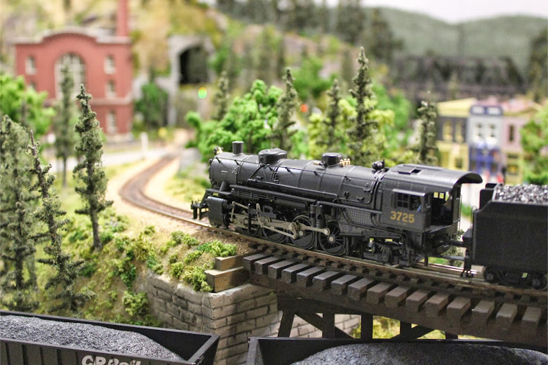 A USRA Light Mikado 2-8-2 steam locomotive crossing a wooden train trestle