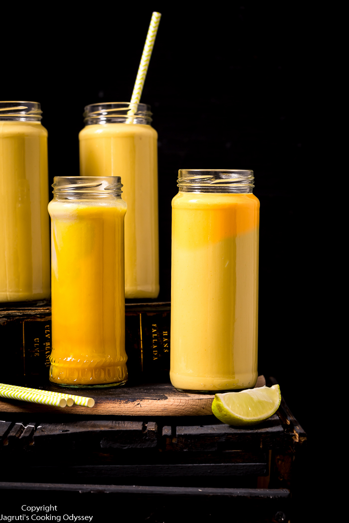 Delicious mango drink served in four bottles and placed on a old book with a wedges of lime.