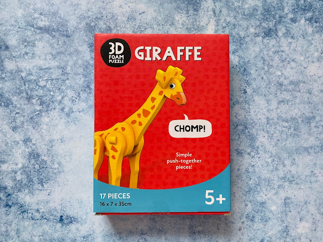 "The 3D foam puzzle giraffe box showing the giraffe with the word ""chomp"" coming out of it's mouth"