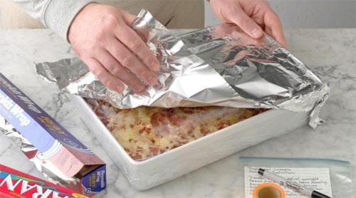 Setelah lasagna Anda dingin, Anda akan ingin membungkusnya dengan erat dengan bungkus plastik dan kertas timah. Ini akan menjaga udara dari mencapai lasagna Anda, mencegah pembekuan freezer dan menjaga rasa dan teksturnya. Untuk melakukannya, bungkus dulu seluruh lasagna, termasuk loyang, dalam bungkus plastik. Cobalah untuk mendapatkan bungkus plastik sedekat mungkin dengan permukaan lasagna untuk menghalangi udara keluar. Kemudian, tutupi bagian atas lasagna yang dibungkus dengan selembar foil untuk mengamankannya. Pelajari cara terbaik untuk menjaga makanan tetap segar dalam freezer dengan trik-trik ini.  Jika Anda membekukan lasagna panggang, Anda juga dapat memecahnya menjadi porsi individual terlebih dahulu. Pindahkan irisan lasagna ke dalam wadah makanan yang aman-freezer atau bungkus irisan pertama dengan bungkus plastik dan kemudian dalam kertas aluminium, dan simpan di dalam tas penyimpanan freezer, seperti tas Ziplock ini. Langkah 3: Beri label Sebelum Anda memasukkan lasagna ke dalam freezer, beri label! Kami suka menulis nama resep, berdasarkan tanggal dan memanaskan instruksi pada selotip cerah dan menempatkannya pada kertas. Anda dapat menulis langsung pada foil, pastikan Anda tidak menusuknya saat menulis. Langkah 4: Bekukan Simpan lasagna penuh atau sebagian dalam freezer hingga tiga bulan. Pastikan freezer Anda mempertahankan 0 ° dengan termometer freezer, seperti ini dari LinkDm.  Catatan: Jika Anda menggunakan piring kaca atau keramik, letakkan lasagna suhu ruangan dalam lemari es selama beberapa jam sebelum membeku, hingga mencapai di bawah 40 °. Perubahan suhu yang terlalu cepat dapat menyebabkan piring pecah, dan pendinginan membantu menjembatani perbedaan. Cara memanaskan ulang lasagna beku  Saat Anda siap menggunakan lasagna beku, pindahkan ke kulkas dan biarkan mencair semalaman. Kemudian, keluarkan dari lemari es dan diamkan pada suhu kamar selama sekitar 30 menit sementara oven Anda memanas hingga 375 °.  Hapus bungkus freezer lasagna, tu