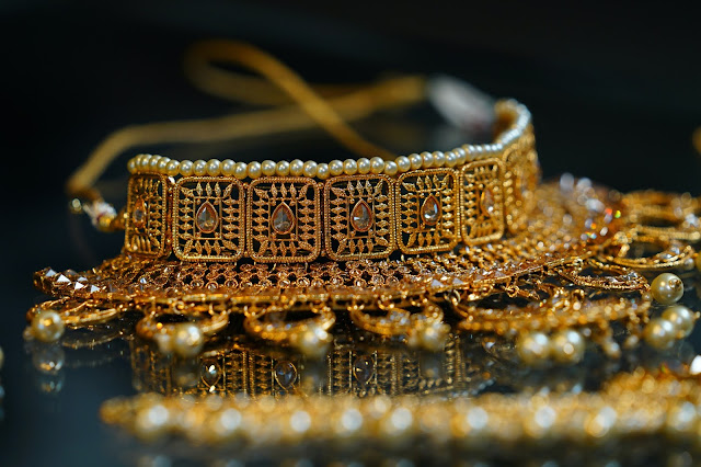 Fine golden jewelry laid out for display on top of a black marble surface.