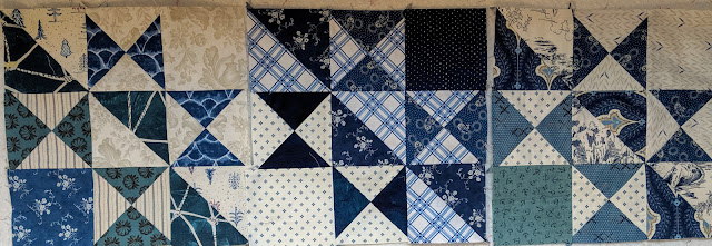 The first three blocks in a variety of blue and white prints laid out on the design wall
