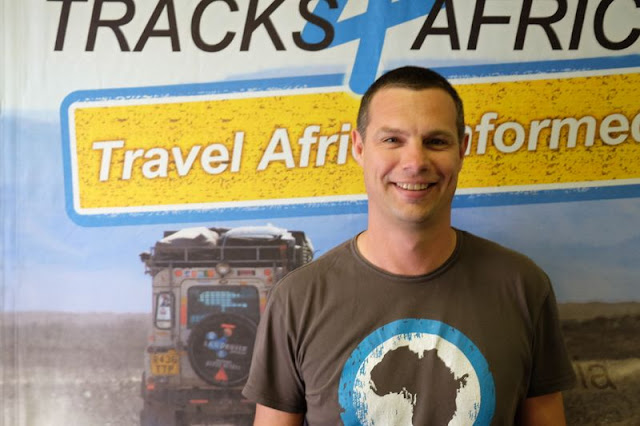 A short-haired smiling man wearing a T-Shirt showing the map of the African continent, in front of a photo mural of a Land Rover on an off-road track.