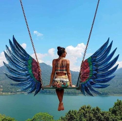 Uma jovem brinca num balanço e nele, tem duas asas gigantes e coloridas.