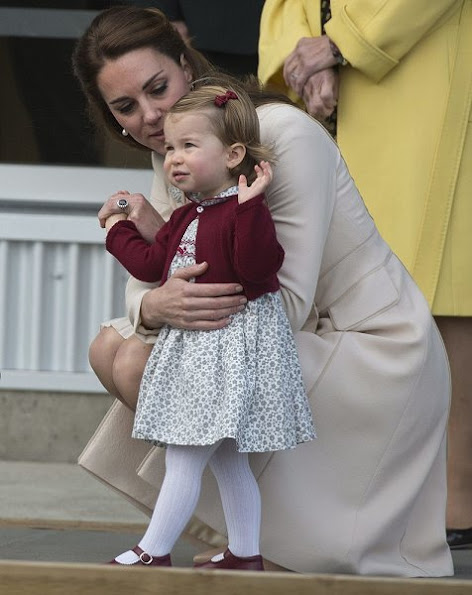 Kate Middleton wore wore a cream coat by Catherine Walker. L.K. Bennett Floret shoes. Cartier Ballon Bleu watch. Annoushka pearls with Kiki McDonough hoops earrings