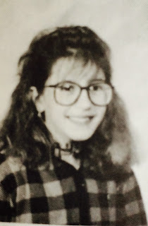 11-year-old girl wearing huge glasses seated for a school portrait wearing an unfortunate plaid shirt.