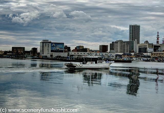 曇り空の船橋漁港。 手前に漁船。 背景にビル群。