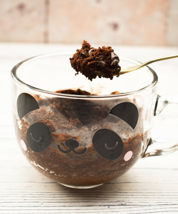 Photo of a spoonful of moist chocolate brownie scooped out of a mug