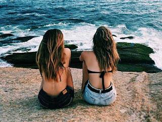 Dos amigas están sentadas juntas en una roca delante del mar, dando la espalda al fotógrafo. Ambas sin camiseta, con vaqueros cortos, uno azul y otro negro.