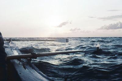 Blick aus einem Ruderboot auf die Ostsee. Die Ruder sind zu erkennen, leichte Wellenbewegung über den Wasser, die Sonne am Horizont.