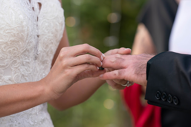 Closeup of Bride putting ring on Groom's finger Magnolia Farm Asheville Wedding Photography captured by Houghton Photography