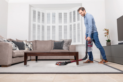 man vacuuming under coffee table with Shark vacuum cleaner