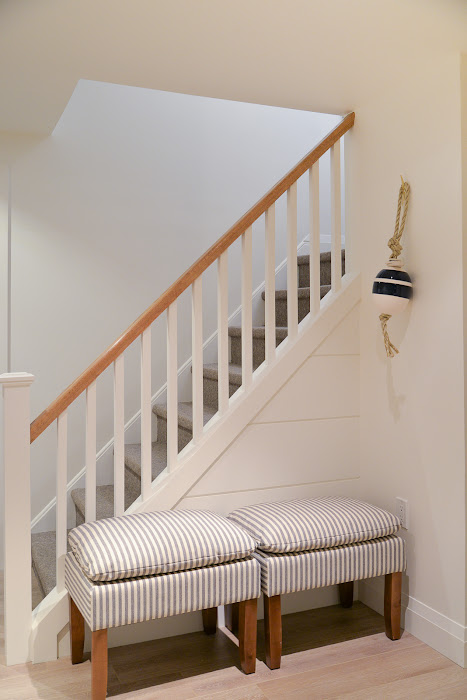 basement stairs with shiplap and striped ottomans; basement stair rail painted