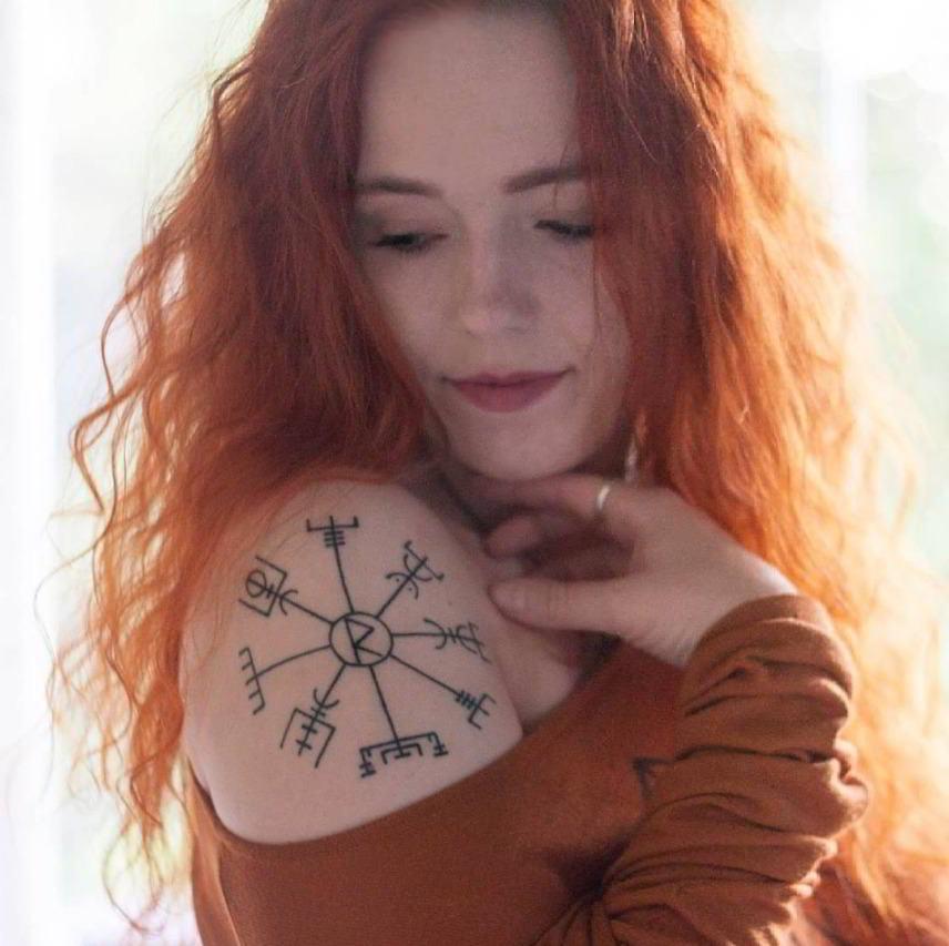 mujer pelirroja con tatuaje de vegvisir en el hombro
