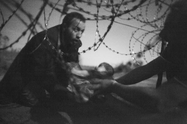 Fotografia di migranti che superano il confine tra Ungheria e Serbia