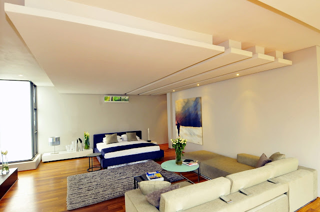 Picture of second bedroom with the blue bed and white sofa by the bed